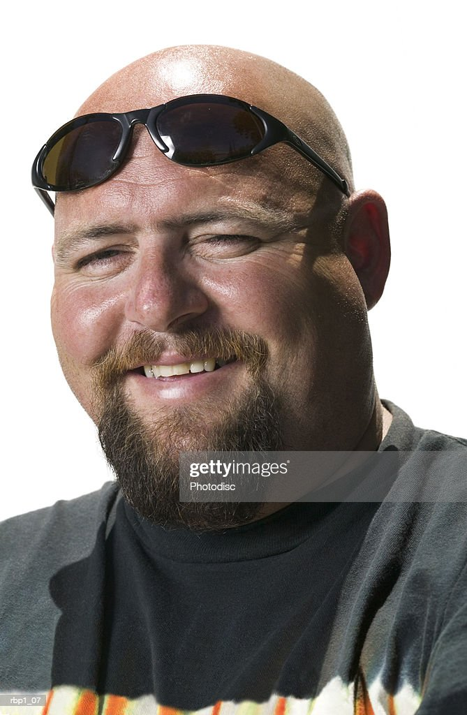 head and shoulders portrait of an adult male in a black shirt and sunglasses as he smiles : Stockfoto