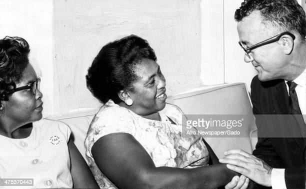 A head and shoulders portrait of civil rights leader Fannie Lou Harmer flanked by a man and woman 1965