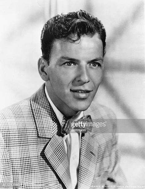 Head and shoulders portrait of entertainer Frank Sinatra wearing a plaid houndstooth jacket and bowtie.