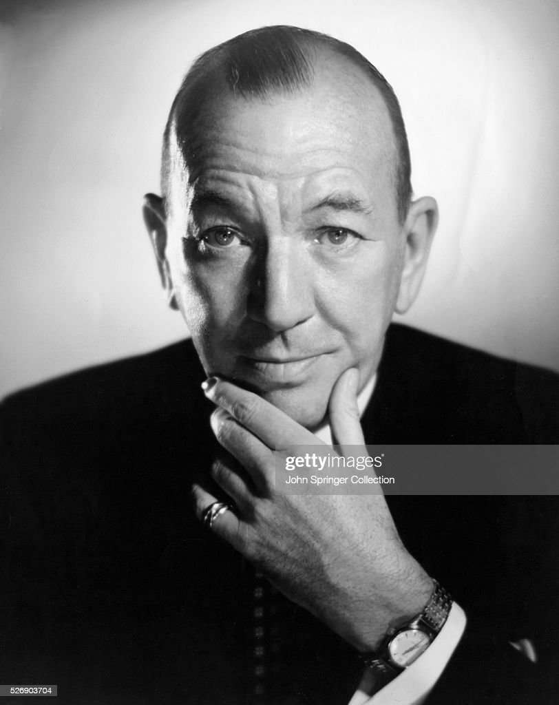 Head and shoulders portrait photo of British actor Noel Coward (1899-1973) with his hand massaging his chin. Ca. 1950.