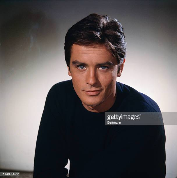Head and shoulders portrait photo of French actor Alain Delon smiling in a black sweater. Ca. 1960s.