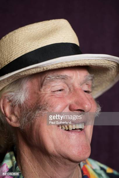 A head and shoulders shot of a happy senior man wearing a hat.