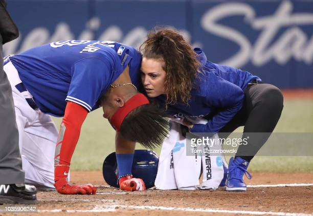 Head athletic trainer Nikki Huffman tends to Lourdes Gurriel Jr #13 of the Toronto Blue Jays after he was hit by pitch in the tenth inning during MLB...