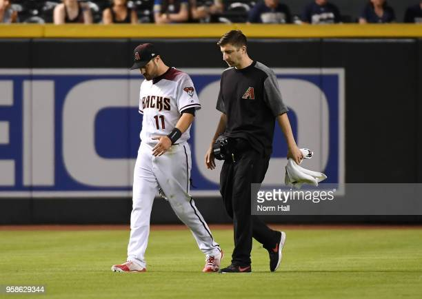 Head athletic trainer Ryan DiPanfilo escorts AJ Pollock of the Arizona Diamondbacks off the field after injuring himself on a dive during the ninth...