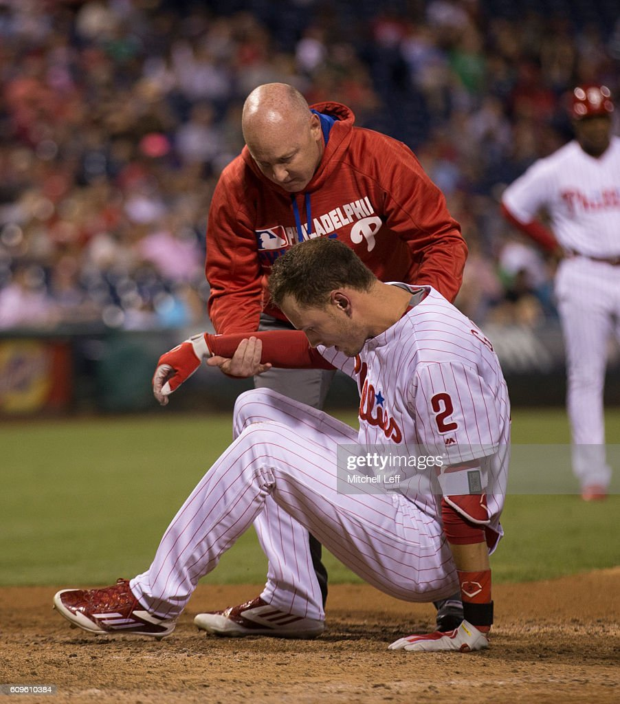 Head athletic trainer Scott Sheridan of the Philadelphia Phillies helps up Tyler Goeddel #2 after he was hit in the head with a pitch in the bottom of the sixth inning at Citizens Bank Park on September 21, 2016 in Philadelphia, Pennsylvania. The Phillies defeated the White Sox 8-3.