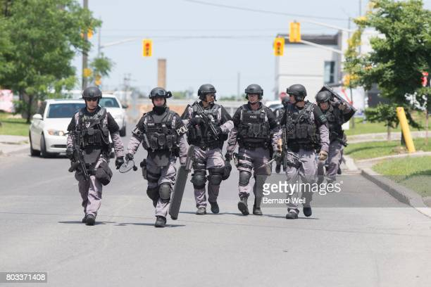 TORONTO ON JUNE 28 ETF head back to their vehicle after a man was led in handcuffs to a waiting police car outside a massage parlour at 85 Kincourt...