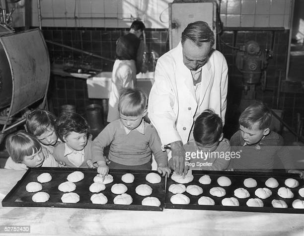 Head baker Alfred Worsten finds a few willing helpers for the task of making 2500 hot cross buns at the Dr Barnardo's Garden Home in Woodford Essex...