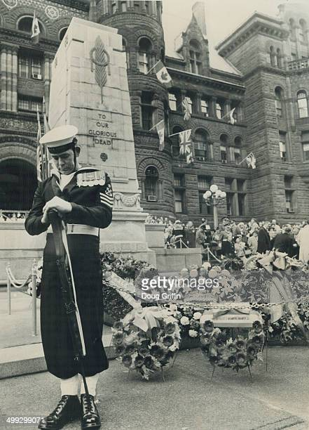 Head bowed over his reversed weapon a seaman from HMCS York stands guard over the wreaths piled before Toronto's Cenotaph in front of the old city...