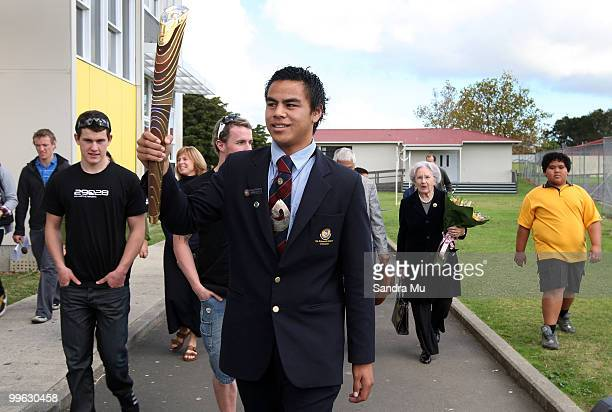 Head boy ArthurTuiafiso holds the Queen's Baton with athletes cyclist Sam Webster swimmer Daniel Bell and Lady June Hillary as part of the Delhi 2010...