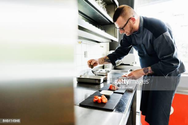 Head Chef Carefully Preparing Starters In Restaurant Kitchen