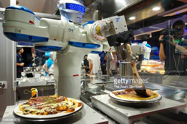 Head chef robot 'Andrew' spread sause on the Okonomiyaki Japanese pancake in the 'Hen na Restaurant ' during the 'Kingdom of Robot' press preview at...