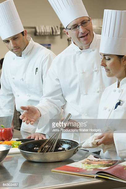 Head chef teaching cooking techniques
