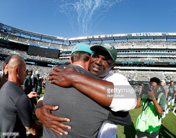 Head coach Adam Gase of the Miami Dolphins and head coach Todd Bowles of the New York Jets meet at midfield after an NFL game at MetLife Stadium on...