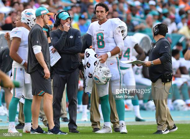 Head coach Adam Gase of the Miami Dolphins speaks with quarterback Brock Osweiler of the Miami Dolphins during a timeout in the fourth quarter...