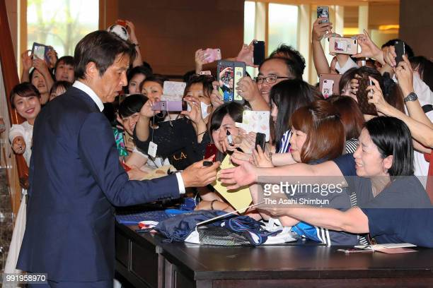 Head coach Akira Nishino of Japan signs autographs for fans after a press conference on July 5 2018 in Narita Chiba Japan