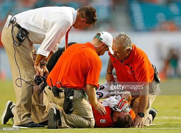 Head coach Al Golden checks on Braxton Berrios of the Miami Hurricanes after he was injured during first quarter action against the Bethune-Cookman...