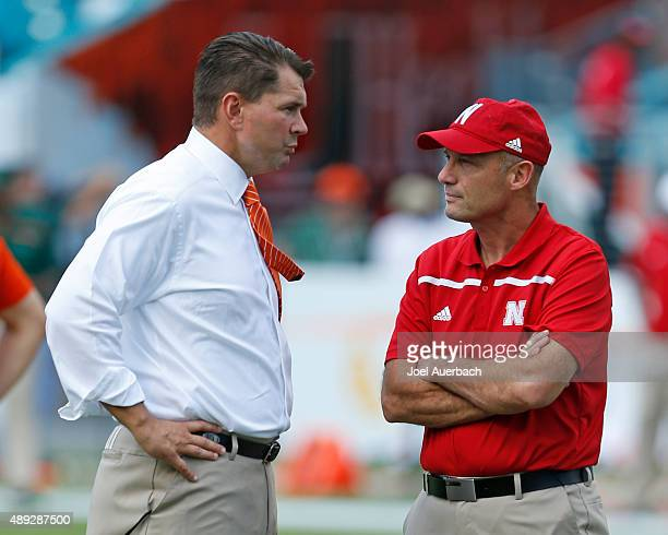Head coach Al Golden of the Miami Hurricanes and Head coach Mike Riley of the Nebraska Cornhuskers talk as the teams warm up prior to the game on...