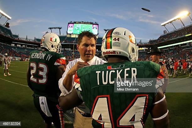 Head coach Al Golden of the Miami Hurricanes congratulates Walter Tucker during a game against the Virginia Tech Hokies at Sun Life Stadium on...