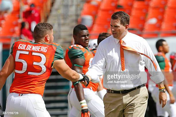 Head coach Al Golden talks to Jared Goldenberg of the Miami Hurricanes as the players stretch prior to the game against the Cincinnati Bearcats on...