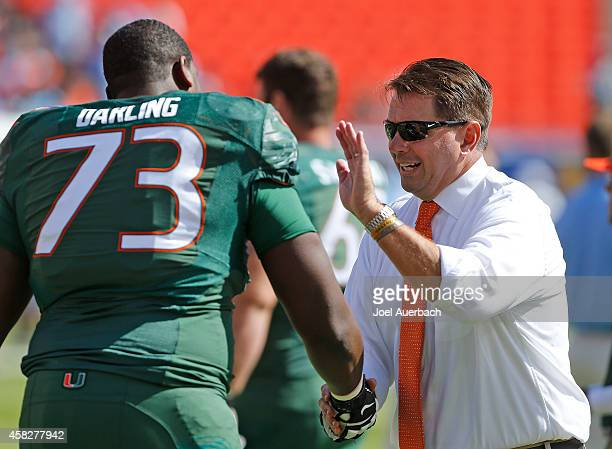 Head coach Al Golden talks to Trevor Darling of the Miami Hurricanes as the team warms up prior to the game against the North Carolina Tar Heels on...