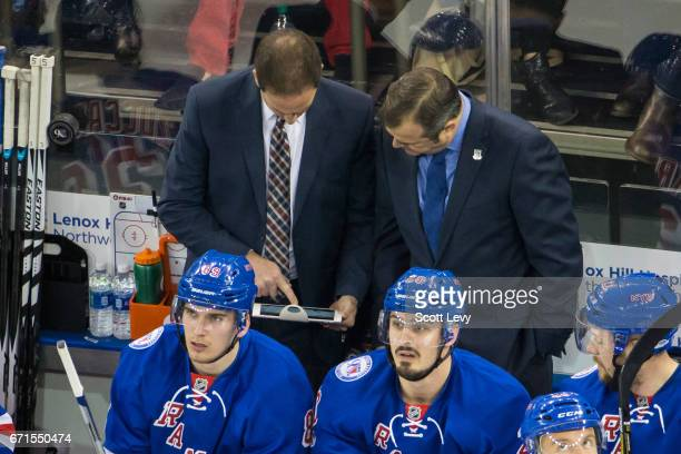 Head coach Alain Vigneault and associate coach Scott Arniel of the New York Rangers review a play on iPads placed on the benches during the game...