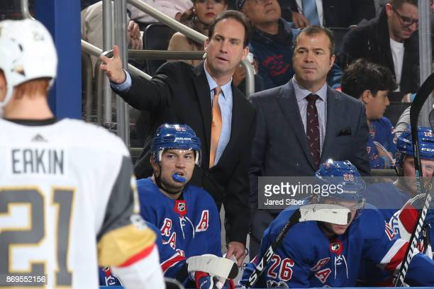 Head coach Alain Vigneault and associate coach Scott Arniel of the New York Rangers look on from the bench against the Vegas Golden Knights at...