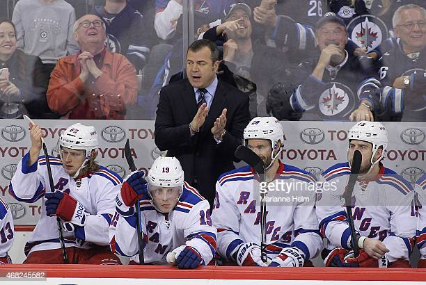 Head coach Alain Vigneault of the New York Rangers claps his hands on the bench in thirdperiod action in an NHL game against the Winnipeg Jets at the...