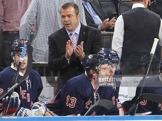 Head Coach Alain Vigneault of the New York Rangers sports a lavender shirt and tie in honor of the Hockey Fights Cancer initiative during the game...
