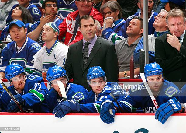 Head coach Alain Vigneault of the Vancouver Canucks looks on from the bench against the San Jose Sharks in Game One of the Western Conference...