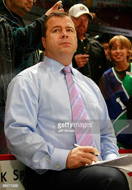 Head coach Alain Vigneault of the Vancouver Canucks sports a pink tie to honour Hockey Fights Cancer as he watches his team during the warmup before...