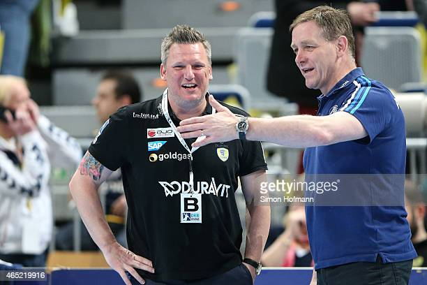 Head Coach Alfred Gislason of Kiel talks to Head coach Nicolaj Jacobsen of RheinNeckar Loewen prior to the DHB cup quarter final match between...