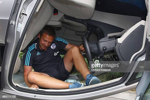 Head coach Andre Breitenreiter climbs out of a turning car during a test drive of Schalke at driving safety centre Rheinberg on August 12 2015 in...