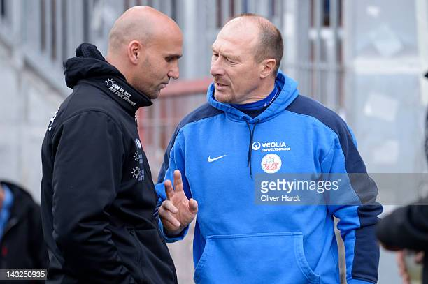 Head coach Andre Schubert of St. Pauli talks with head coach Wolfgang Wolf of Rostock talking before during the 2 Bundesliga match between St.Pauli...