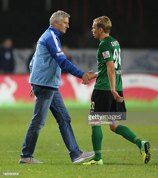 Head coach Andreas Bergmann of Rostock shakes hands with Dennis Grote of Muenster after the Third League match between Preussen Muenster and Hansa...