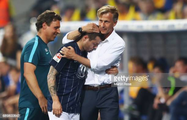 Head coach Andries Jonker of Wolfsburg hugs Vieirinha after his substitution during the Bundesliga Playoff leg 2 match between Eintracht Braunschweig...