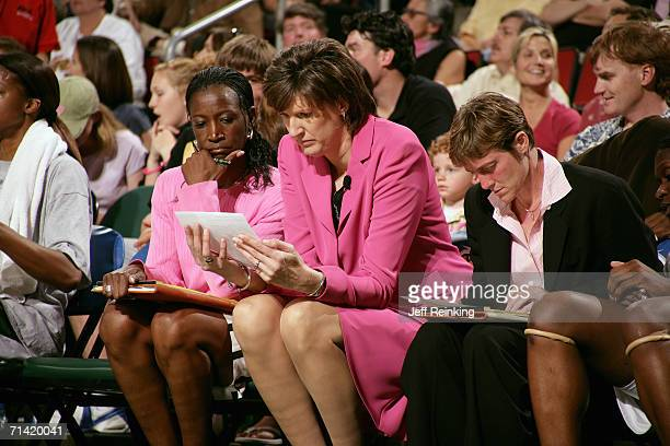 Head coach Anne Donovan assistant coach Jessie Kenlaw and athletic trainer Annmarie Henkel of the Seattle Storm talk on the bench during a game...