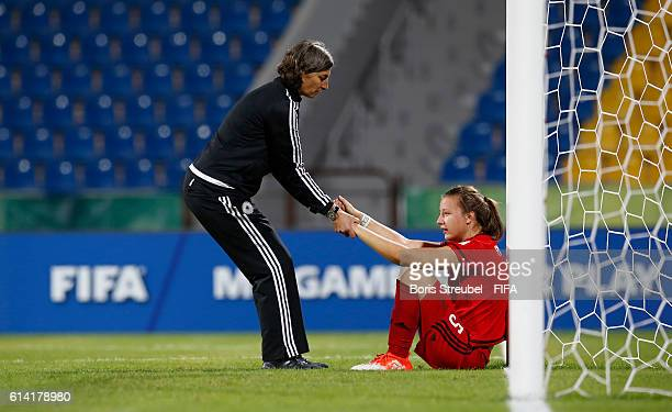 Head Coach Anouschka Bernhard of Germany gives team mate Tanja Pawollek of Germany a legup after losing the FIFA U17 Women's World Cup Quarter Final...