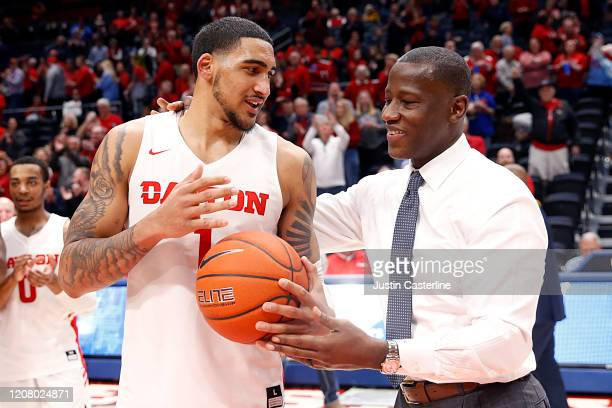 Head coach Anthony Grant of the Dayton Flyers presents the game to Obi Toppin of the Dayton Flyers for joining the 1000 point club after the game...