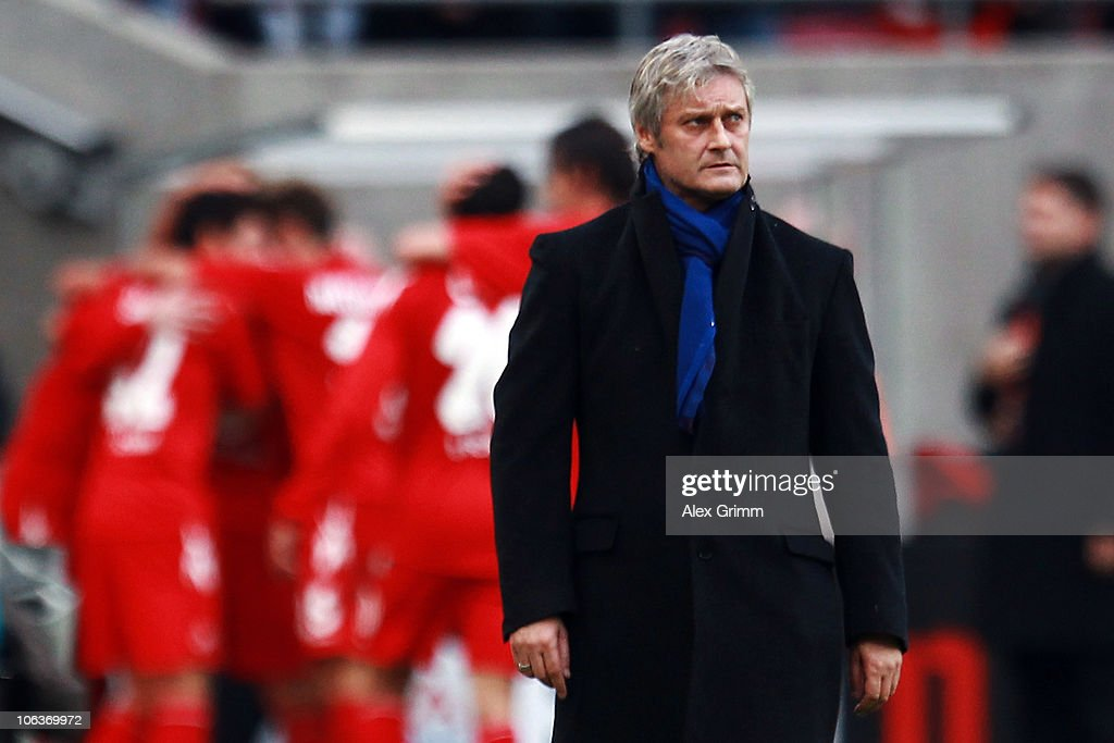 Head coach Armin Veh of Hamburg reacts as Milivoje Novakovic of Koeln and team mates celebrate their team's third goal during the Bundesliga match between 1 FC Koeln and Hamburger SV at the RheinEnergieStadion on October 30, 2010 in Cologne, Germany.