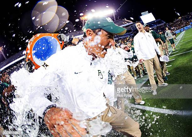 Head coach Art Briles of the Baylor Bears has water dumped on him after the Russell Athletic Bowl game against the North Carolina Tar Heels at...