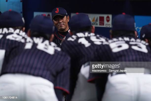 Head coach Atsunori Inaba of Japan watches while players huddle prior to the game six between Japan and MLB All Stars at Nagoya Dome on November 15...