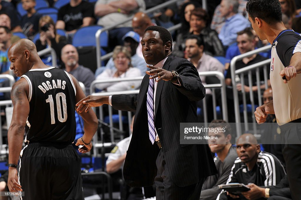 Head Coach Avery Johnson of the Brooklyn Nets speaks with one of his players from the sidelines as Keith Bogans #10 smiles and looks on against the Orlando Magic during the game on November 30, 2012 at Amway Center in Orlando, Florida.