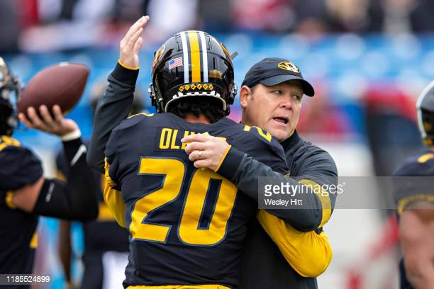 Head Coach Barry Odom gives a hug to Khalil Oliver of the Missouri Tigers before a game against the Arkansas Razorbacks at War Memorial Stadium on...