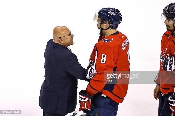 Head coach Barry Trotz of the New York Islanders shakes hands with Alex Ovechkin of the Washington Capitals after their 2-0 victory in Game Five to...