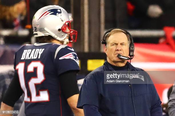 Head Coach Bill Belichick looks on as Tom Brady of the New England Patriots walks by during the AFC Championship Game against the Jacksonville...