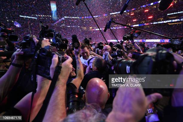 TOPSHOT Head Coach Bill Belichick of the New England Patriots and quarterback for the New England Patriots Tom Brady are surrounded by journalists as...
