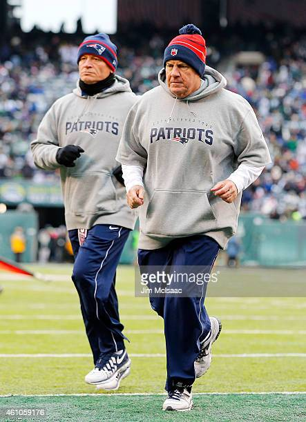 Head coach Bill Belichick of the New England Patriots runs off the field after the first half against the New York Jets on December 21 2014 at...