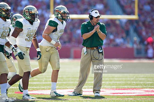 Head Coach Bill Clark of the UAB Blazers claps for his team as the run onto the field during a game against the Arkansas Razorbacks at Razorback...