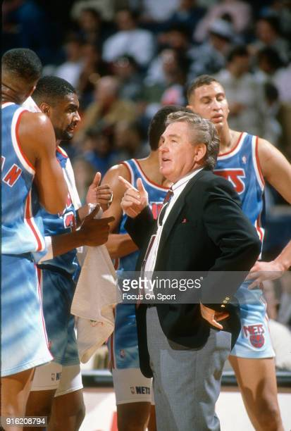 Head coach Bill Fitch of the New Jersey Nets talks with his team while there's a time out during an NBA basketball game against the Washington...