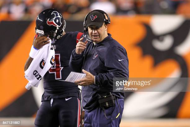 Head coach Bill O'Brien of the Houston Texans looks on while talking to Deshaun Watson against the Cincinnati Bengals during the first half at Paul...